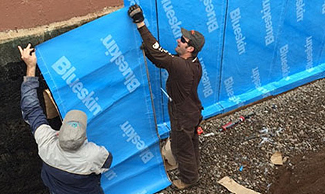 Workers putting up waterproof barrier
